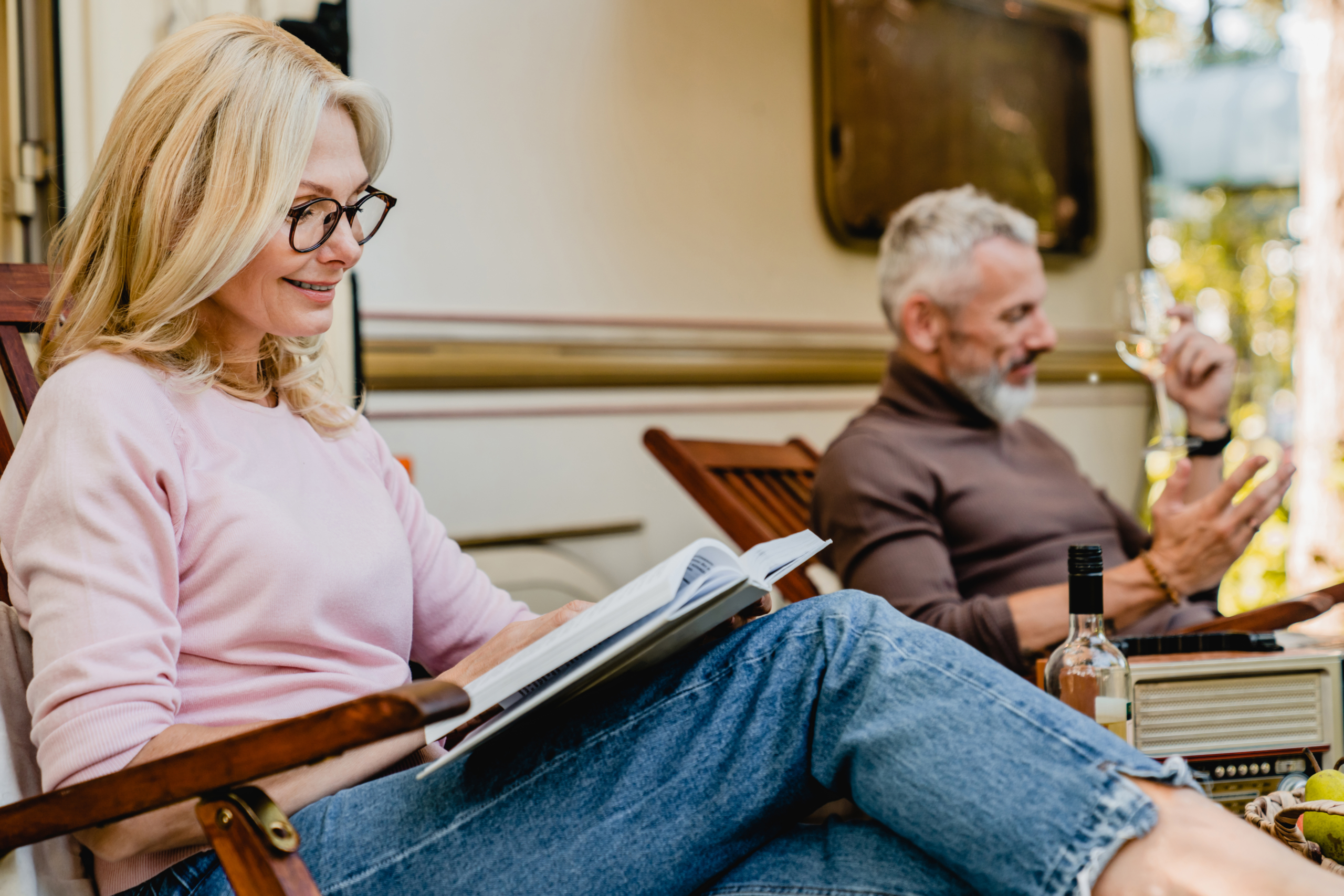 mature couple sitting outside their caravan reading books and drinking wine